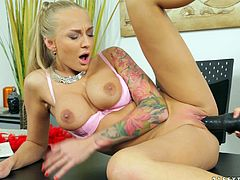 Tattooed busty blondie gets her soaking poontang licked and fingers brunette babe's pussy. Thereafter hotties poke each other's clams with a strapon.