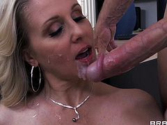 Lovely blonde cowgirl with big tits unleashes his hard dick and gives it a blowjob before drilling her hardcore in the office as she fondles her tits