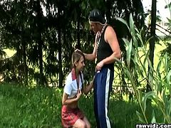 Pigtailed teen in school uniform banging in forest