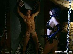 Torrid brunette MILF looks damn gorgeous wearing kinky leather outfit. Dominatrix crucified her sex slave and whipped him mercilessly. Then, she ordered him to lick her pussy.