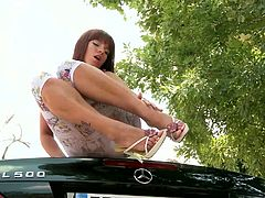 Dizzy dark-haired enchantress takes off her clothes demonstrating her appetizing booty and hot boobs. Then she lies on the hood of the car and dildos her snapper.