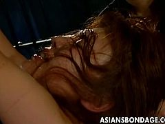 Asian sex slave feeling helpless together with her master in the dungeon. She let herself got her two hands tied up while mashing her boobs and her one leg to spread her hairy pussy for some toying action.