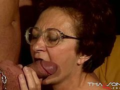 Four-eyed granny gives head to a young stud in provocative old and young porn video