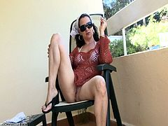 Salacious brunette mom wearing a bikini and fishnet dress, is getting naughty on a balcony. She smokes a cigarette, then sits down on a chair and plays with her snatch.