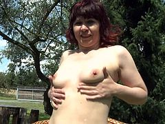This sexy redheaded mature slut is looking nice in her lingerie and she teases us while sitting on her wicker chair in the backyard. She rubs her pussy and plays with her saggy, natural boobs. Her light skin is glorious.