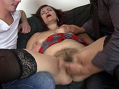 This mature slut has her way with two young men. She will show them how it's done. The sexy older lady gets her boobs licked as she grabs their crotches, and then she opens her legs so that they can play with her hairy cunt.