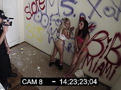 This sexy lesbian couple, one brunette and one blonde, are making out in a graffiti covered abandoned warehouse. A filmmaker catches them fucking and spies on them. They don't mind being filmed, so they invite him to join in on the action.