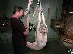 This blonde slave has a ball gag in her mouth and rope tied around her limbs. Her mean master lifts up one of her legs with rope and uses a hitachi vibrator of her cunt until she can't take it anymore. He pulls on the rope and raises her up to the ceiling until she is completely lifted off the ground.