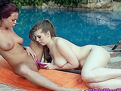 Glamorous busty lesbian brunettes using sextoys by the pool in bikini