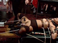 Veruca is tied to the table with rope and the master is increasing the speed on the fuck machine, that is pounding her cunt hole. In the other side of the room another slave has to get down on her knees, to suck cock.