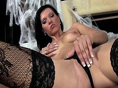 Sexy brunette in witch costume rubs herself