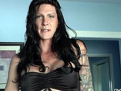 Horny Shemale hooker in black with tattoos sits on the couch and jerks of before busting her cum load in solo masturbation