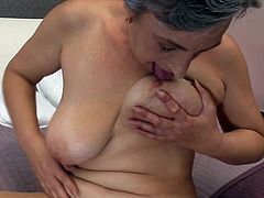This nasty granny is lying back on the bed in her underwear. The old skank takes her bra off and juggles her natural boobs. Her tits are so saggy, that she can lick her own nipples. What a freaky slut!