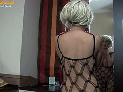 This amateur blonde has a pair of huge natural boobs and a nice, round ass. She reveals both while she fingers her tight cunt, dressed in a bodystocking suit.