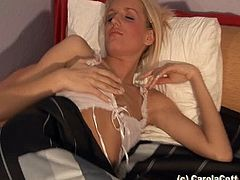 Admirable blonde Carola Cott, wearing stockings, shows her shaved cunt for the cam. Then she pleases herself with fingering and moans sweetly.