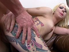 Tattooed chick with long blonde hair enjoying a hardcore doggy style fuck