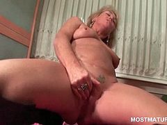 Tattooed mature in boots working her starving snatch in bed