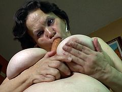 The camera catches some nice intimate close ups of a mature lady, who loves to play dirty alone. The brunette versed slut is naked and begins to masturbate, when laying in bed. She's got big boobs and wears makeup. The atmosphere gets pretty intense, when she starts sucking the dildo and squeezes her tits.