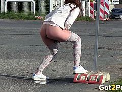 Dirty black haired chick pisses near road sign a lot