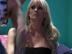 Mouth-watering blonde Stormy Daniels with long blond hair, big breasts and sexy legs turns guy on to the point of no return. Hot woman in short black dress bares her assets and spreads her legs invitingly.