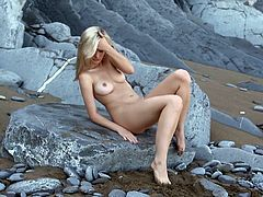 Anna adores walking nude on the rocky sandy shore. This hot blonde-haired slut has an incredible body and wonderful natural tits. She is like a rough diamond and there's something really magic in her lusty regards. See her laying down, legs opened widely...