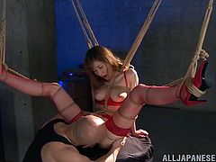 This bound slave is tied up tightly with rope and she has her legs spread wide, so her master has access to that beautiful cunt. The cute Japanese chick squirts all over the place, after she is fingered and has a sex toy used on her clit.