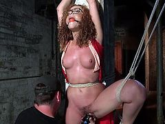 With a ball gag in her pretty mouth, this redheaded slut is hogtied and hung upside down from the ceiling, so her master can inflict pain and pleasure upon her sultry body. The vibrator makes her cunt wet.