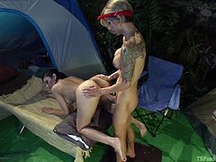 A slutty short-haired blonde shemale relaxes in a charming brunette's company, during their trip in the woods. See naughty Beretta, sucking and licking cock with fervor. Click to watch the tattooed ladyboy rimming ass and fucking the busty brunette from behind, as they step out from their cozy tent.