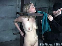 Horny dude fixes obedient busty blondie in pillory and cuts her dress