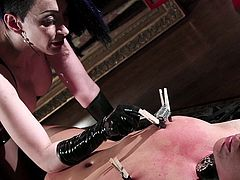 Dominatrix in latex plays with her bound slave girl