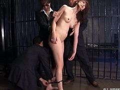 Asian slave girl in a jail cell is controlled and used by men