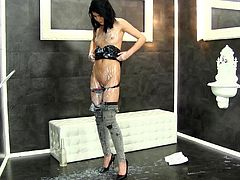 What is that sticking out of the hole in the wall? It looks like it's a massive cock. She walks over and sucks, and tugs. The cock shoots on her tight jeans, and then on her panties, and then all over the place. She takes it deep in her cunt and the cum keeps on flowing. Will it ever stop?