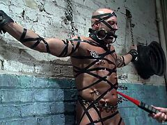 Christian has Coby right where he wants him. Tied to a wall with leather straps and a steel bar, gagging his mouth. He zaps him with an electric wand a few times, before breaking out the hose and spraying him all over.