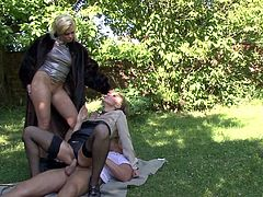 Elegantly clothed ladies have a threesome in the grass