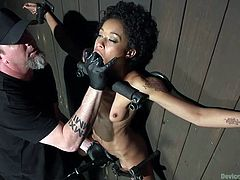 Skin is in the twisted bondage device, where she is on the wall, body open to what her executor may think of to do to her. She sucks his gloved fingers, as he puts them in her mouth, then fingers her pussy, making her scream.