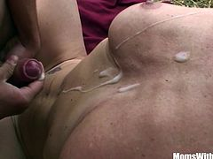 Sexy blonde mature mom fucks two young studs out in the grassy fields.