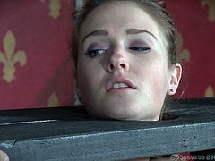 Ashley is tightly wedged in a single-board version of stocks. The topless beauty now has rubber bands stretched all over her face. She doesn't want one of those things to snap against her, so she keeps still, until the cattle prod zips her a little.
