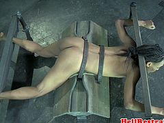 Bound ebony sub in pillory gets spanked