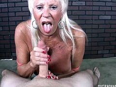Mature milf comes in on her friend masturbating totally naked. She decides to give him hand so starts stroking it and when hes about to cum she puts it in her mouth for a blowjob till he shoots a big load in her mouth.