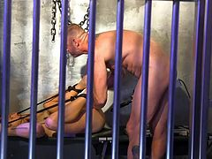 Nate is tied to the bunk in this cell. He's also getting fucked by a machine placed down there. As if that wasn't enough, D. is there, also cramming his asshole full of cock. He does get tantalized some as the device comes off his cock and D. strokes him teasingly.