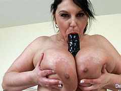 Huge tits British mature Carol Brown oils up her massive melons and dildo fucks her juicy cunt