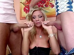 A sexy blonde whore in lingerie and fishnets, gets it on with two