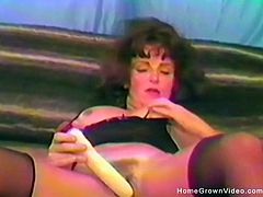 Sexy dark haired mature in lingerie and heels spreads her legs to reveal her hairy pussy then stuffs her fuck hole with toys
