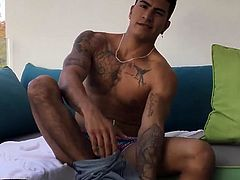 Our featured solo boy of the week is Erick a sexy young Latino, with a muscular and inked smooth body. He slowly strips naked, revealing that big uncut dick of his and with the help from some oil he soon has it stiff and ready for action. Kicked back on a sofa, Erick flexes as he strokes his big meat. With a body like that, every second of his jerk off session is totally captivating. Finally, the young man stands and pumps a cum load into his waiting hand.